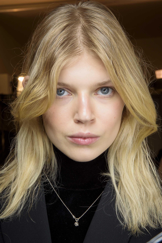 Une femme blonde avec une frange de rideau porte des coiffures longues pour des visages ronds
