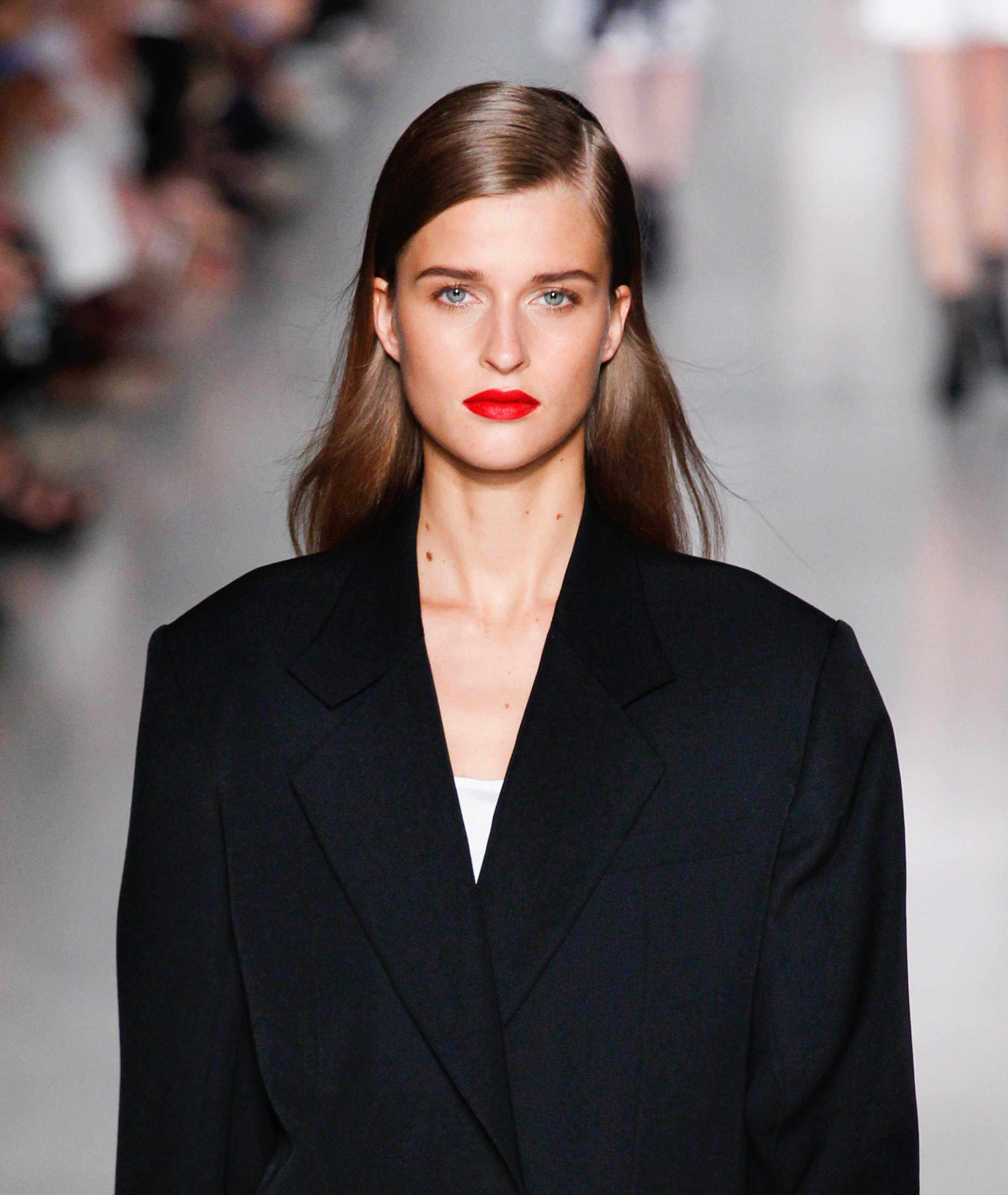 Des coiffures pour des visages ronds : Femme brune avec une raie latérale portant du rouge à lèvres rouge