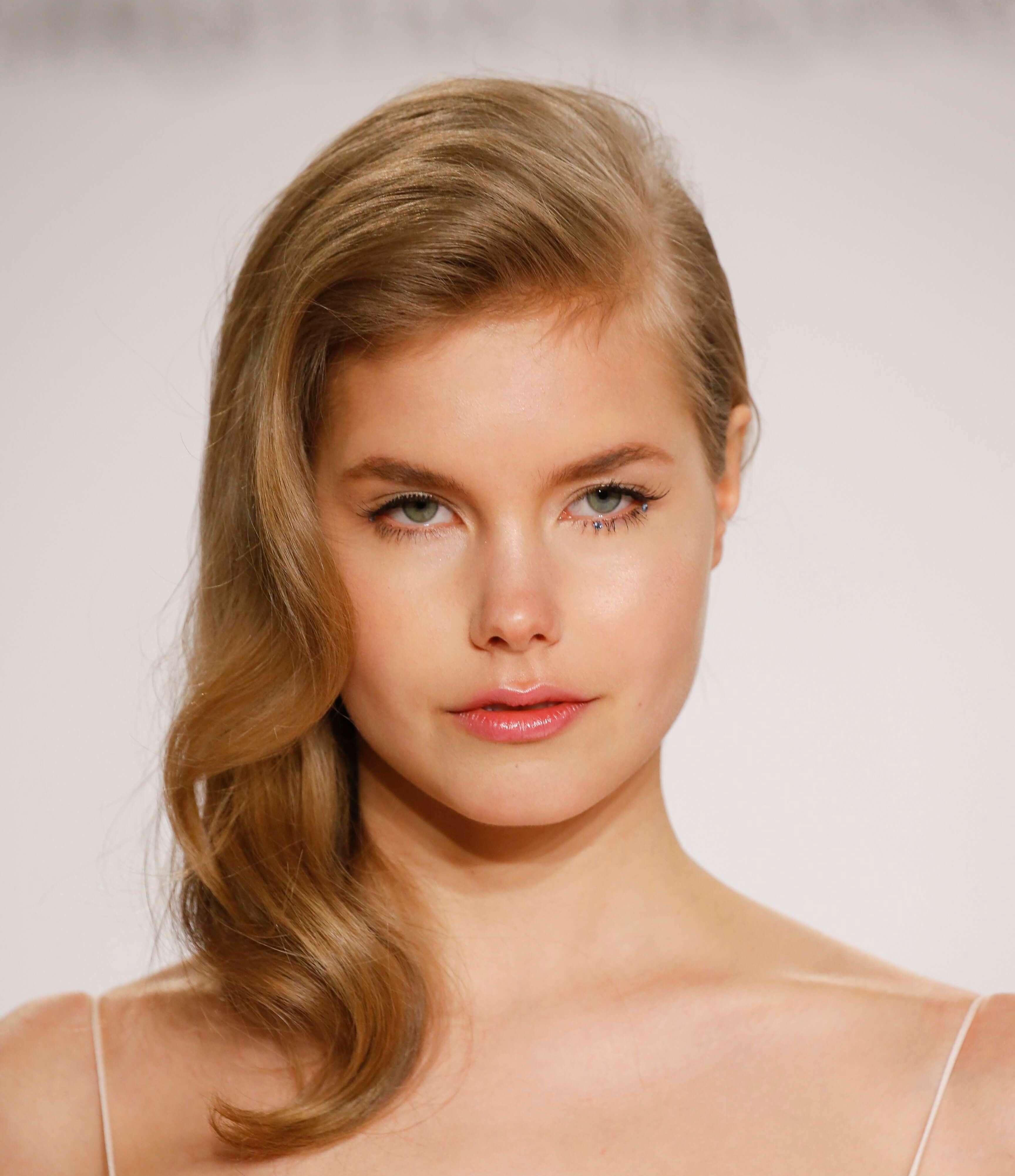 les meilleures coiffures pour les visages ronds : Femme blonde de taille moyenne avec une frange balayée sur le côté