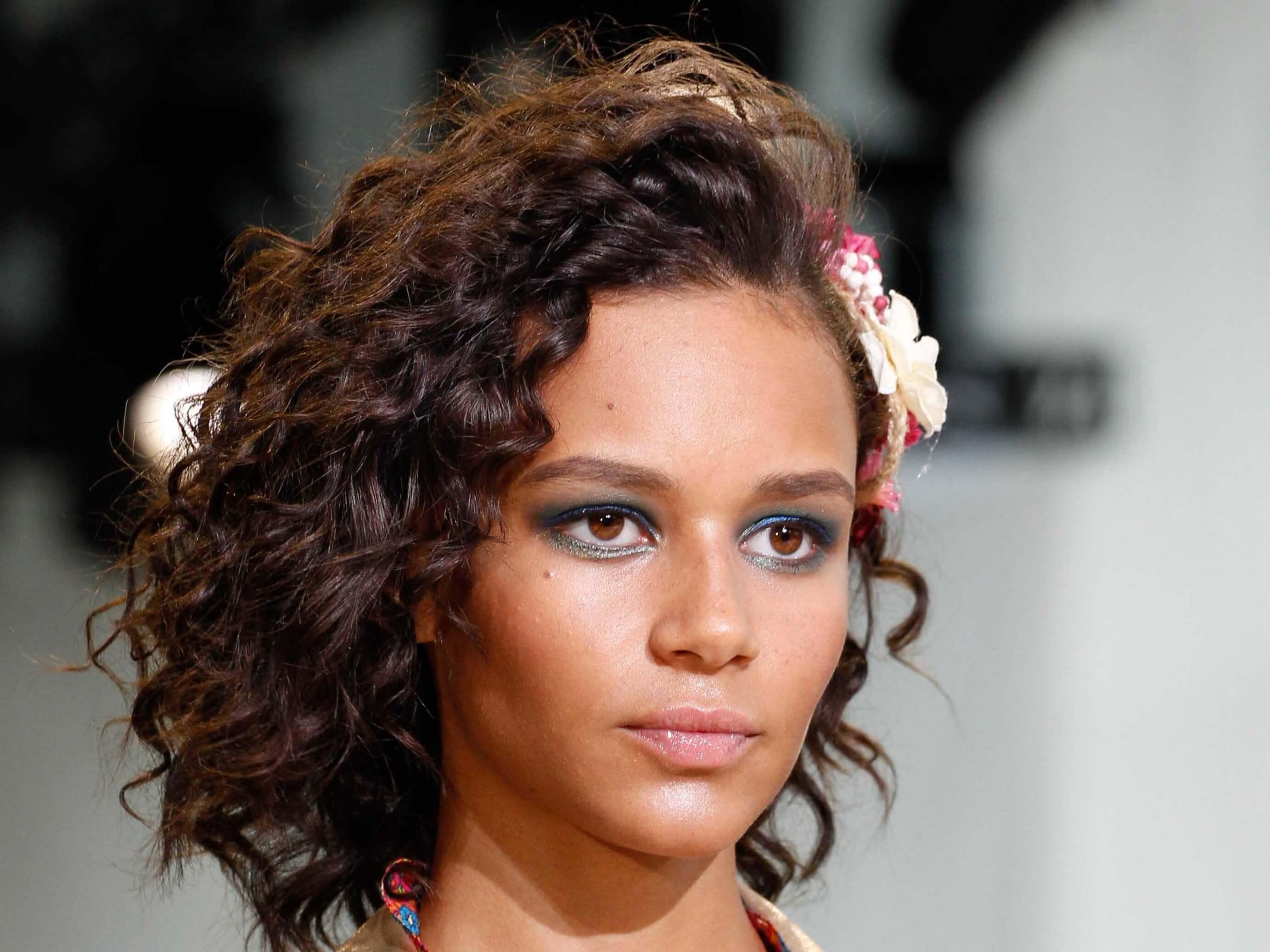 Coiffures pour visages ronds : mannequin de mode féminine avec une coiffure courte et bouclée sur la piste