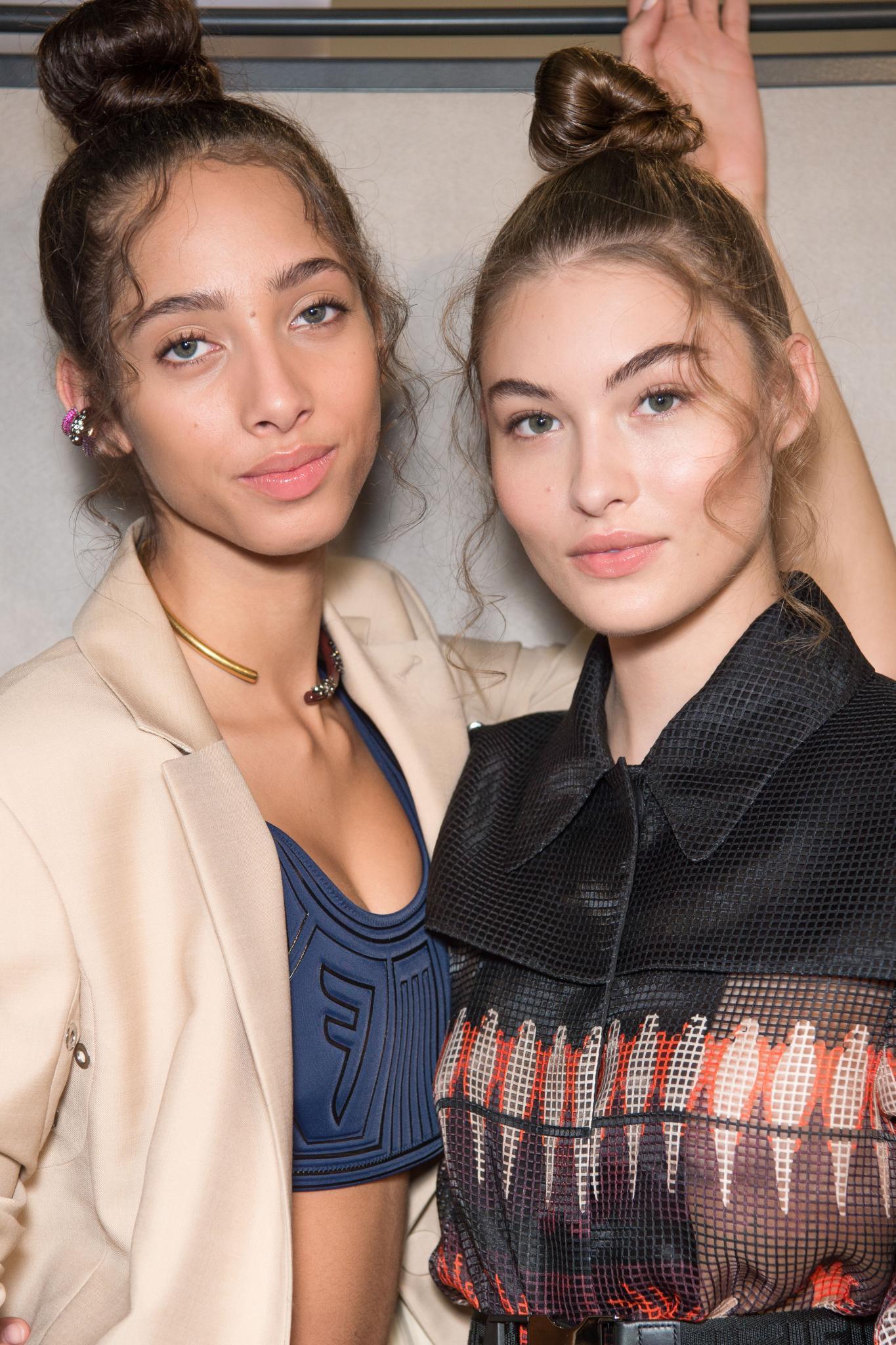 Deux mannequins dans les coulisses de Fendi, avec des cheveux volants et filiformes, coiffés en topknot, portant des vêtements Fendi et posant pour la photo