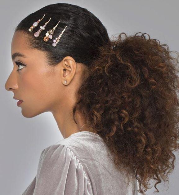 Accessoires de coiffure pour la fête : Modèle avec des cheveux bruns naturellement bouclés en queue de cheval basse et lisse, avec des cheveux en cristal qui glissent sur le devant des cheveux.