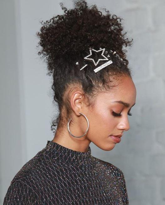 Accessoires de coiffure pour la fête : Femme aux cheveux bruns naturellement bouclés en haute queue de cheval avec des épingles à cheveux ornées de bijoux et qui se glisse sur le devant des cheveux.