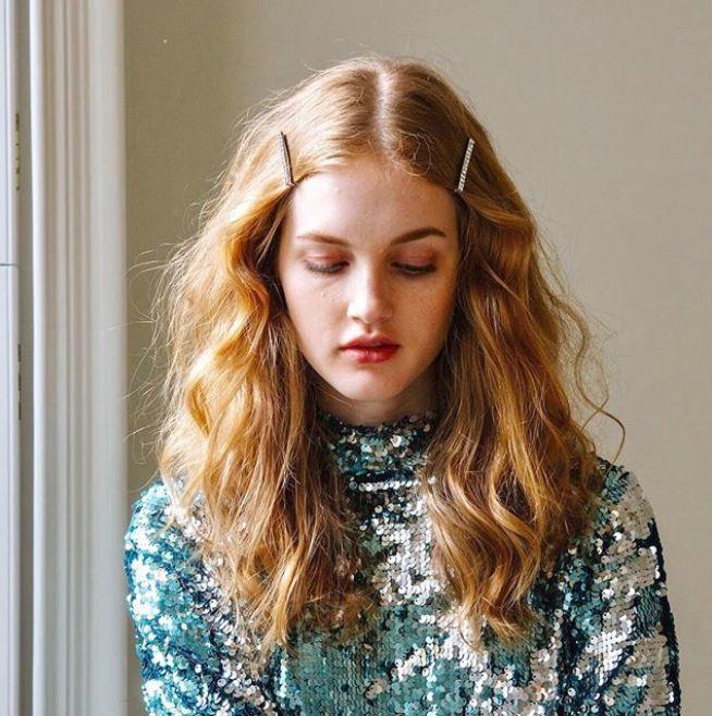 Accessoires de coiffure pour la fête : Femme aux longs cheveux ondulés blond fraise avec des mèches de cheveux à la tempe, portant un haut à paillettes.