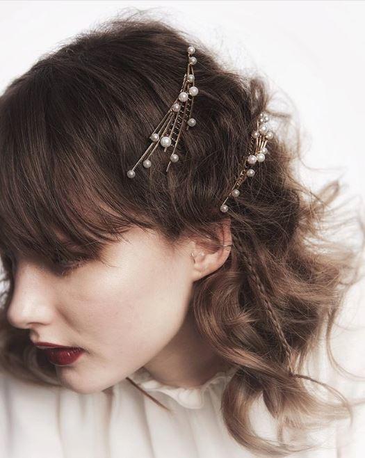 Accessoires de coiffure pour la fête : Femme aux cheveux bruns ondulés à la longueur des épaules avec des épingles à cheveux en perles sur le côté.