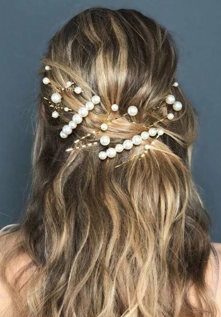 Accessoires de coiffure pour la fête : Femme aux cheveux blonds ondulés et mis en valeur, coiffée dans un style mi-haut, mi-bas, ornée d'accessoires capillaires en perles.
