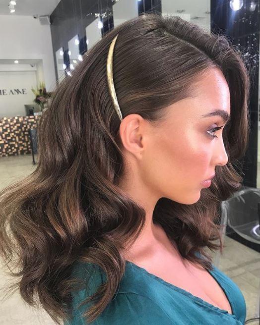 Accessoires de coiffure pour la fête : Femme avec de grandes vagues rebondissantes sur des cheveux bruns de longueur moyenne avec une seule barrette dorée épinglant le côté arrière.