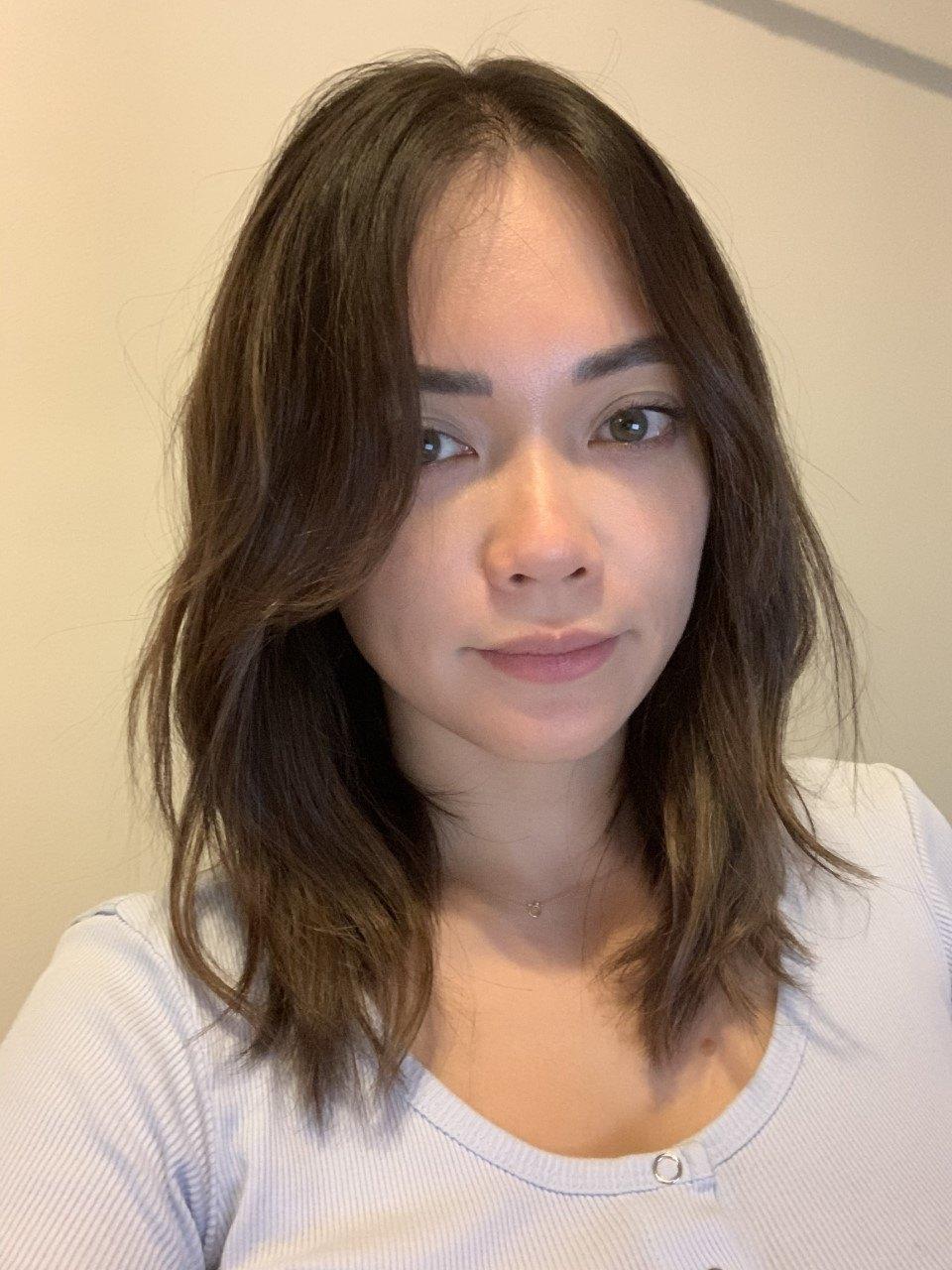 femme aux cheveux bruns ondulés de longueur moyenne
