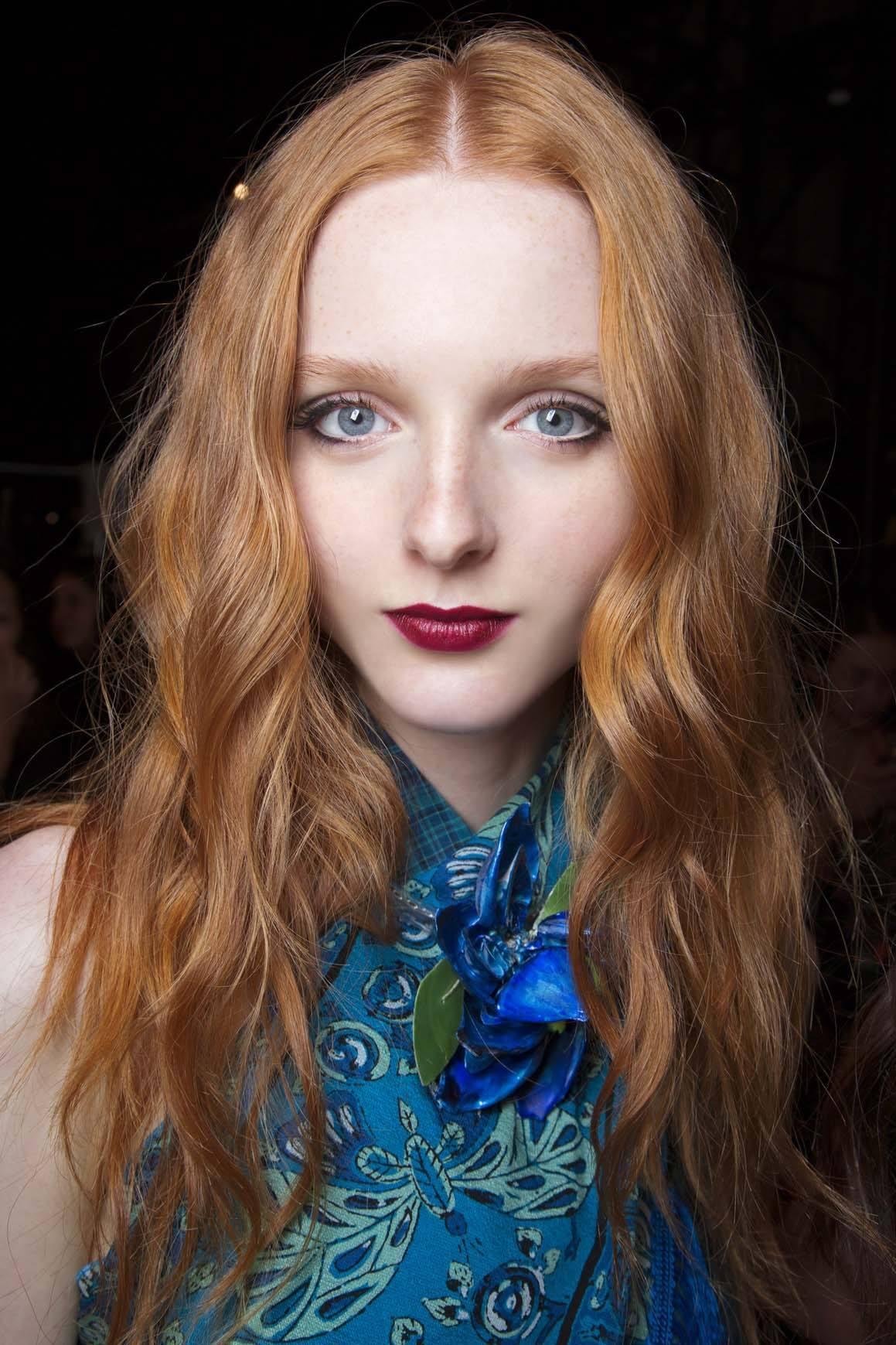 mannequin à la peau claire avec de longs cheveux ondulés roux cuivrés et gingembre, portant un haut bleu et du rouge à lèvres à base de baies