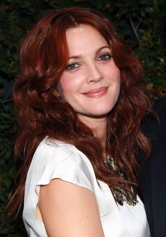 Les cheveux roux : Drew Barrymore avec de longs cheveux roux foncés en finition bouclée, portant un t-shirt blanc.