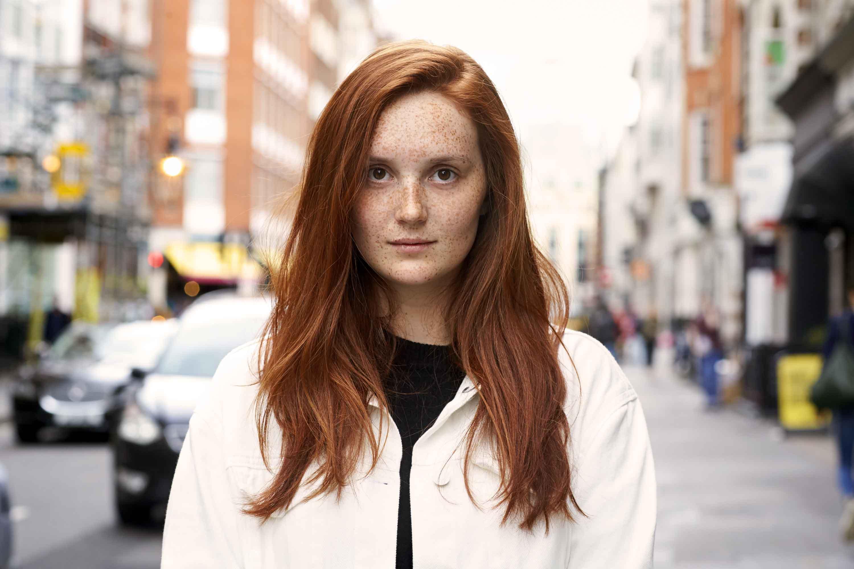 femme dans la rue avec de longs cheveux roux épice citrouille avec raie sur le côté