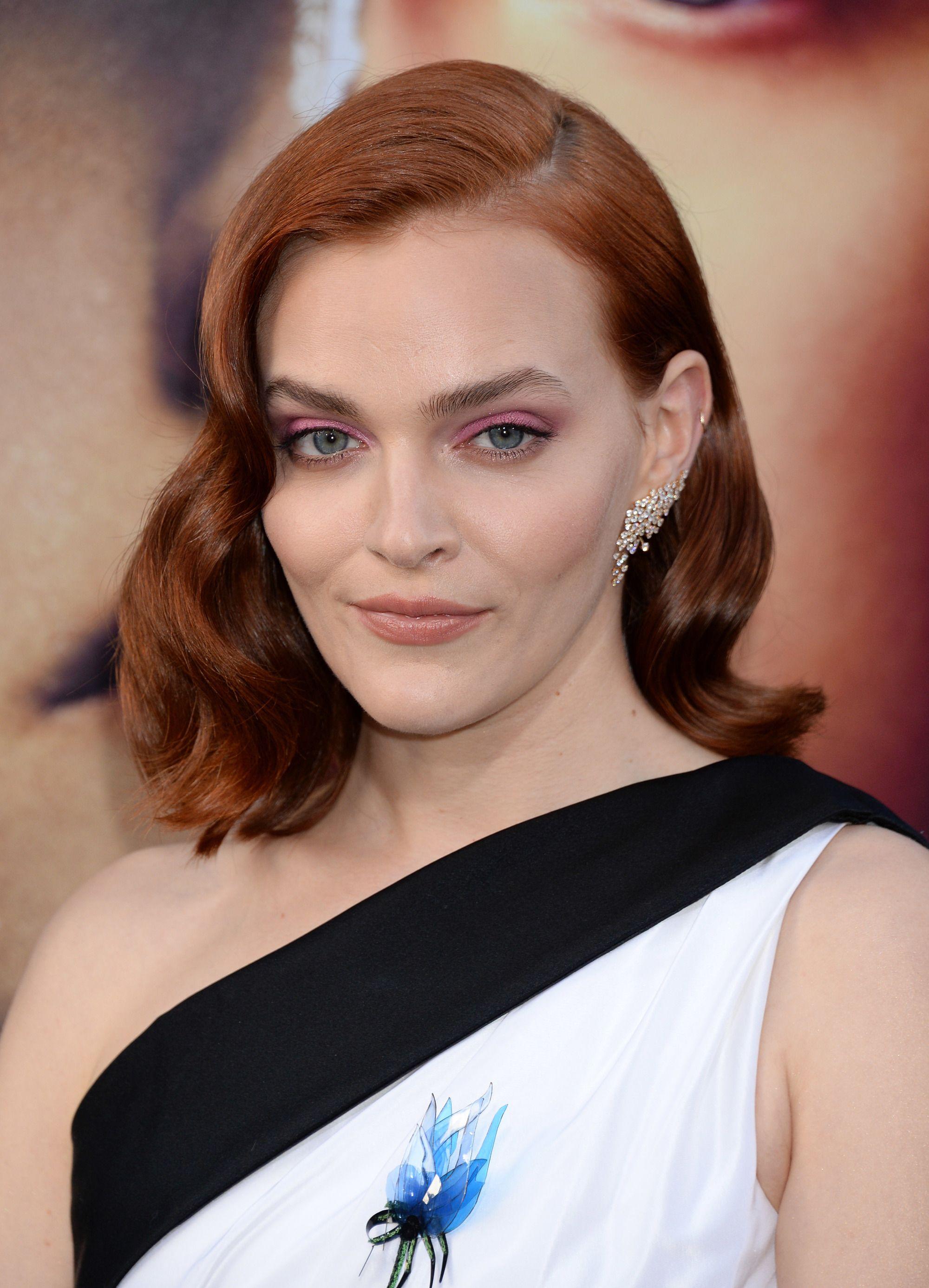 Madeline Brewer avec des cheveux roux aux épaules avec des ondulations hollywoodiennes et portant une robe à l'épaule.