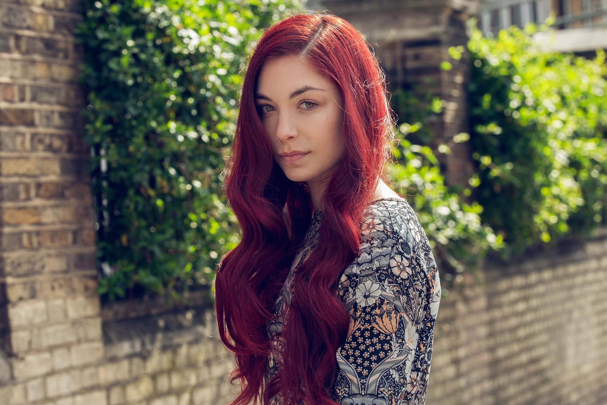femme aux longs cheveux roux cerise avec un top à motifs ondulés et à côtés