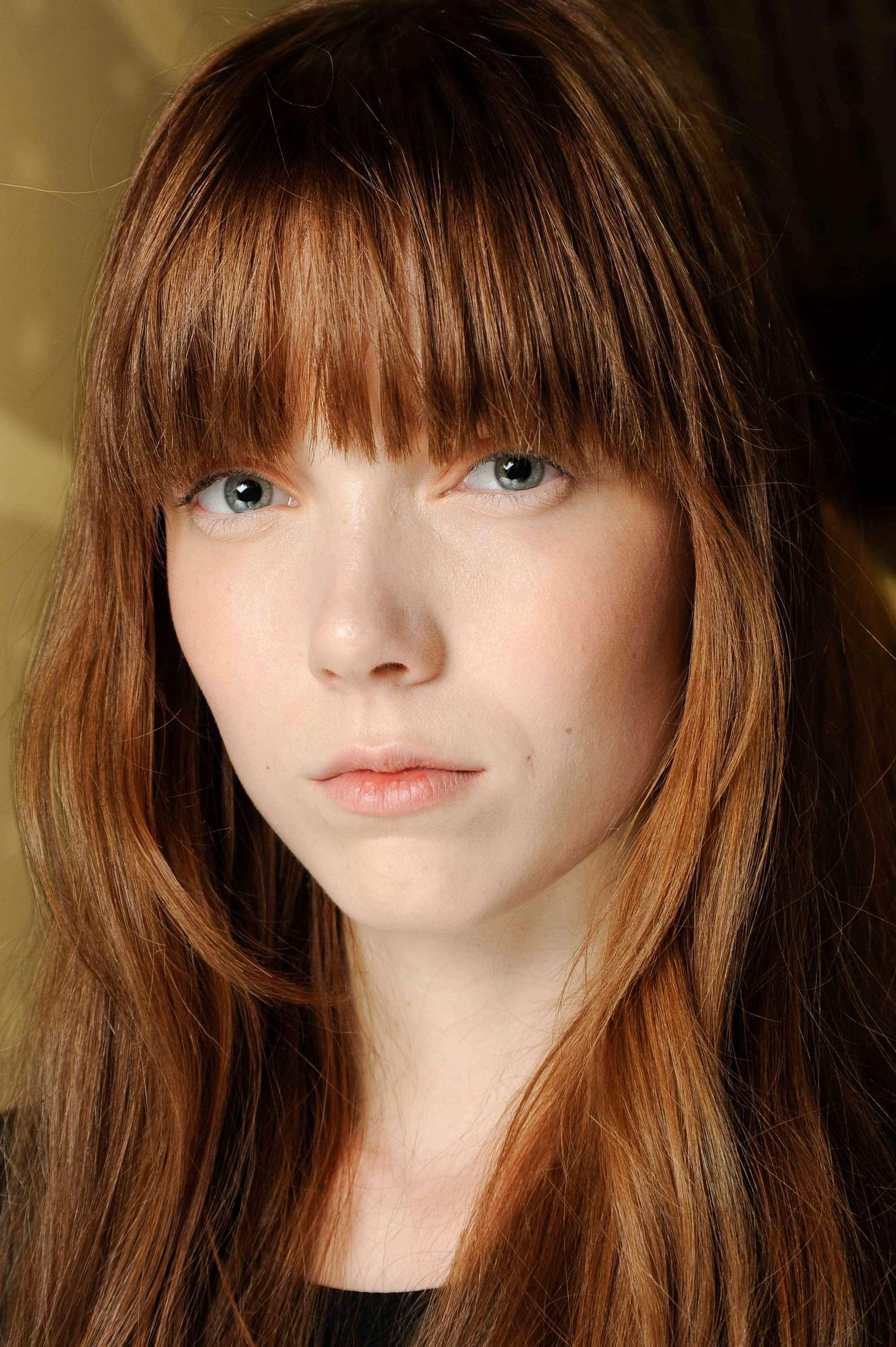 modèle avec des cheveux mi-longs lisses brun-rouge auburn avec une frange complète