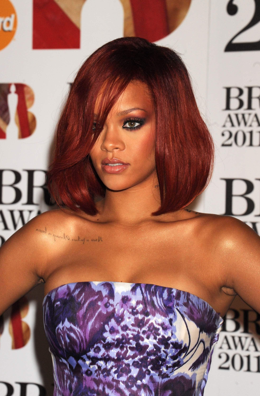 rihanna aux brit awards, avec des cheveux roux profonds et longs, une frange balayée par les raies latérales et une robe violette sans bretelles