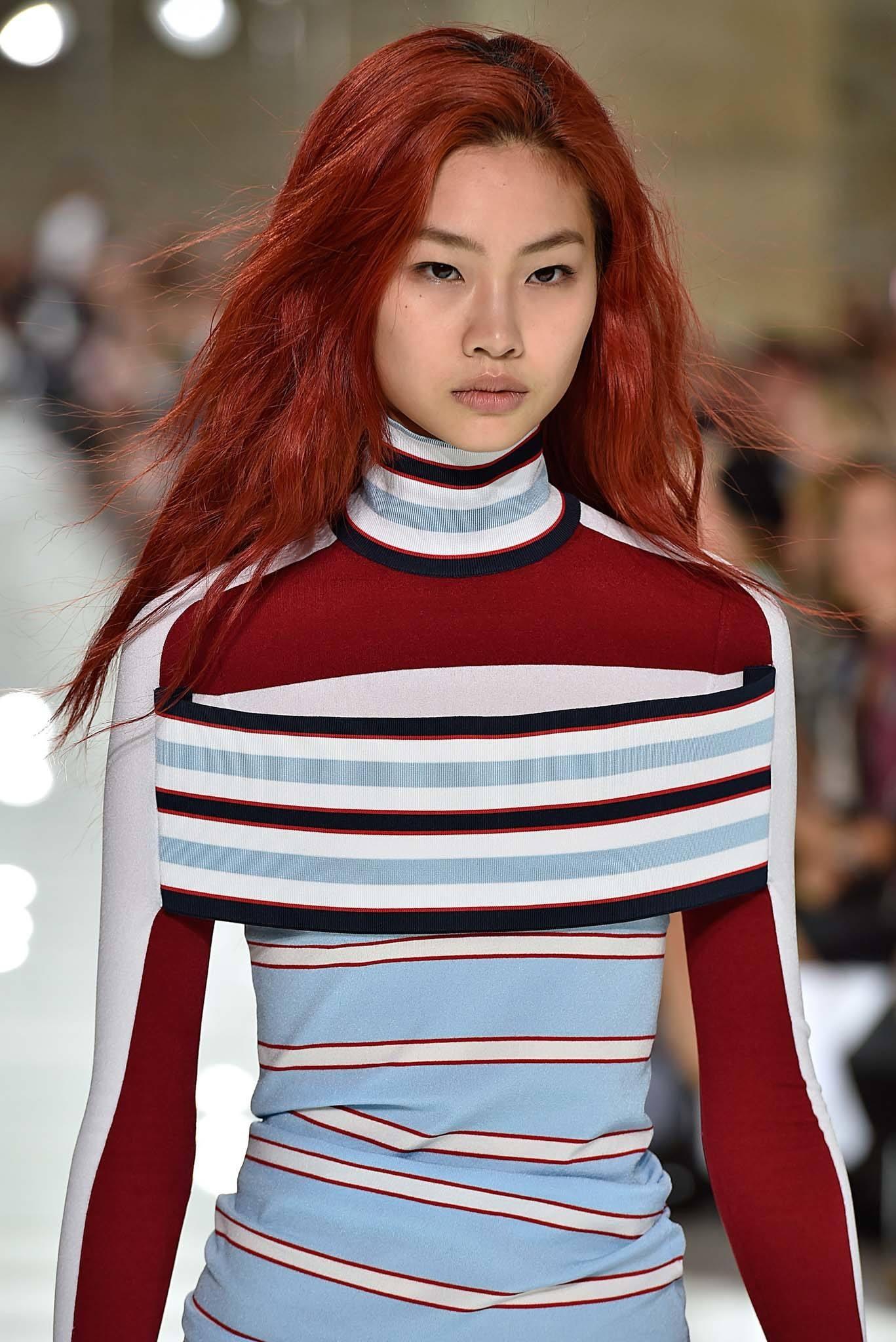 Modèle sur la piste avec de longs cheveux roux ébouriffés portant une tenue rayée au SS18 de Louis Vuitton.