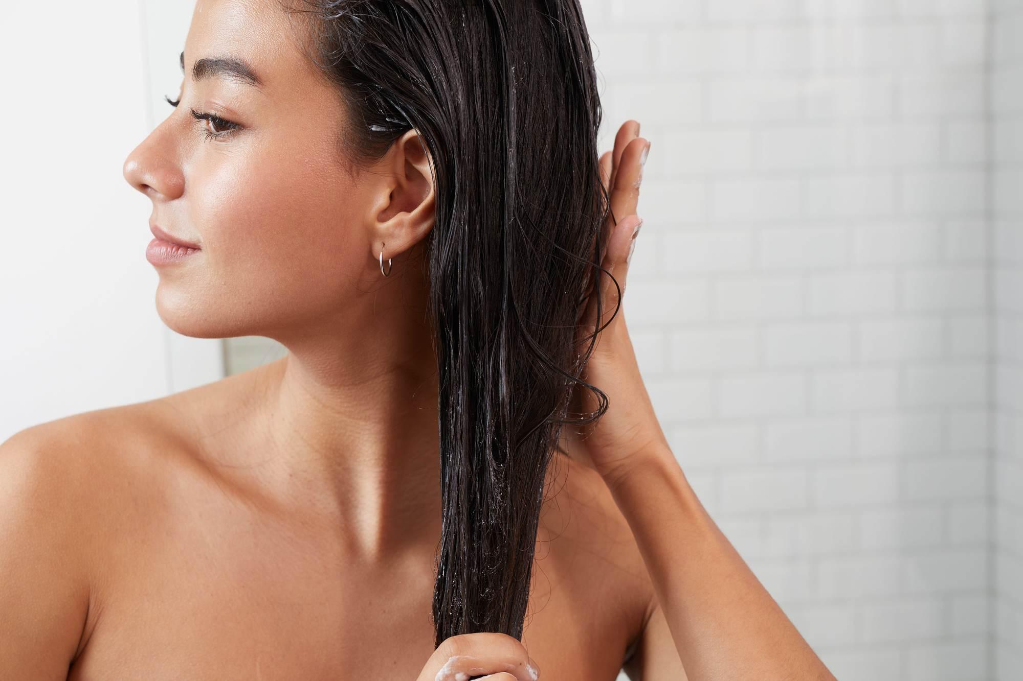 Femme aux cheveux bruns foncés appliquant un après-shampoing sur ses cheveux mouillés