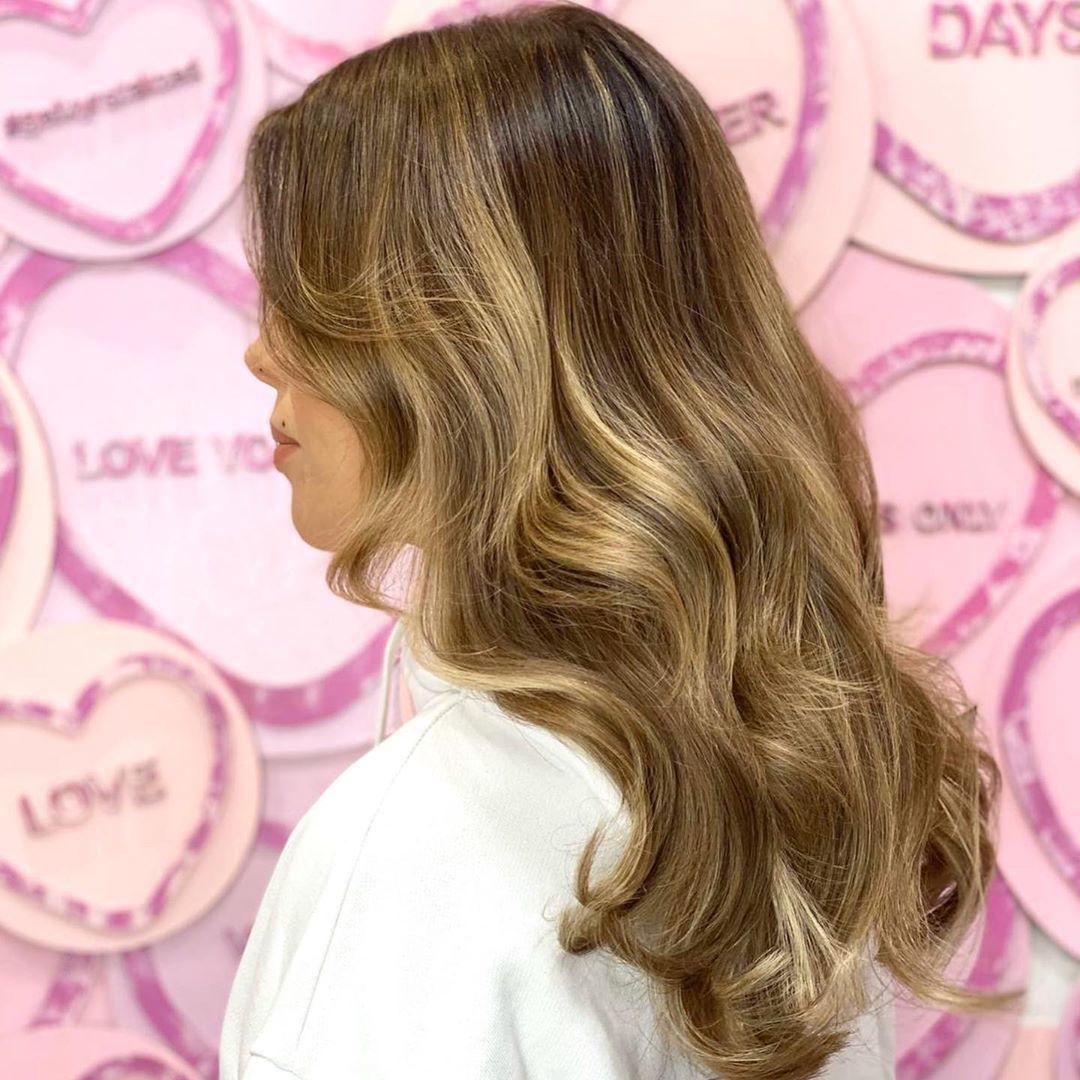 Femme aux cheveux caramel b;londe aux mèches ondulées
