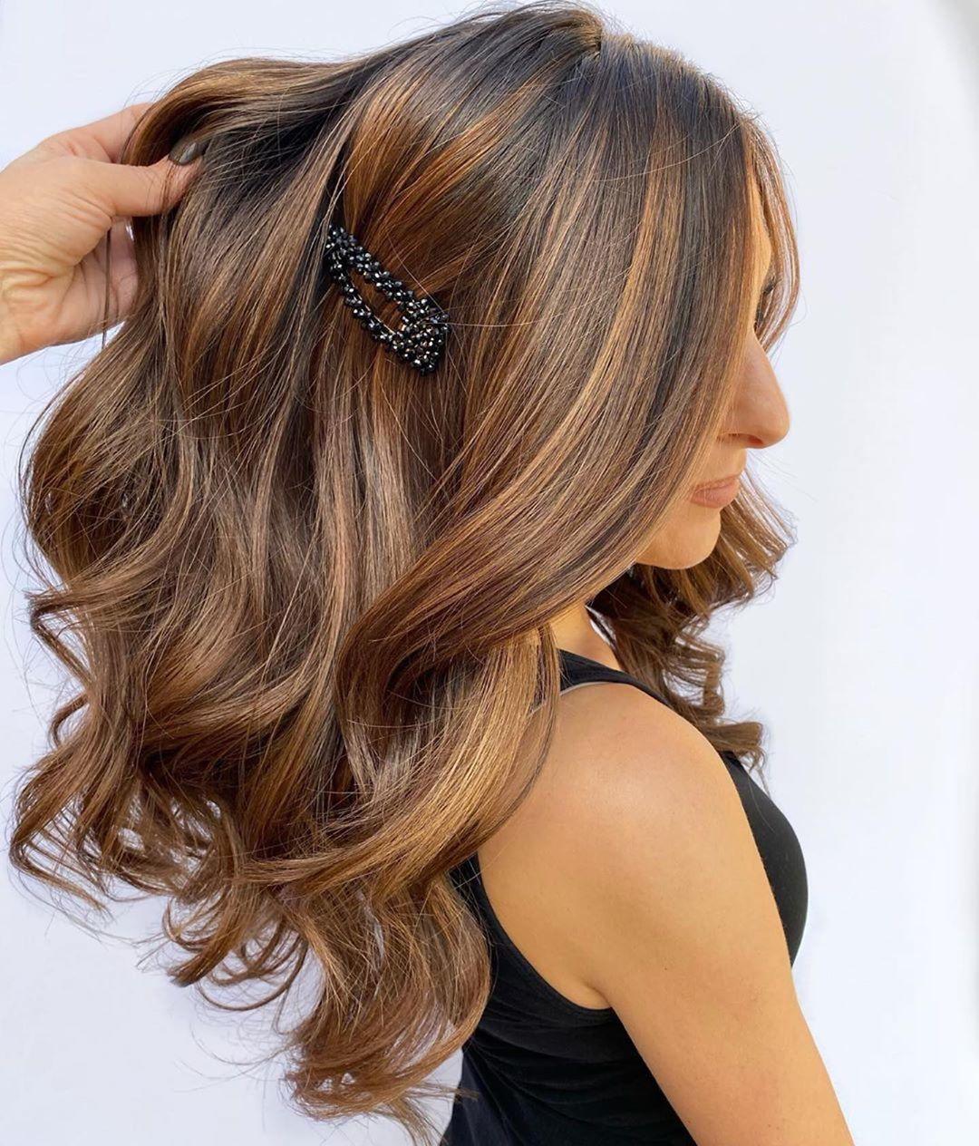 Femme aux cheveux châtain foncé avec des reflets caramel