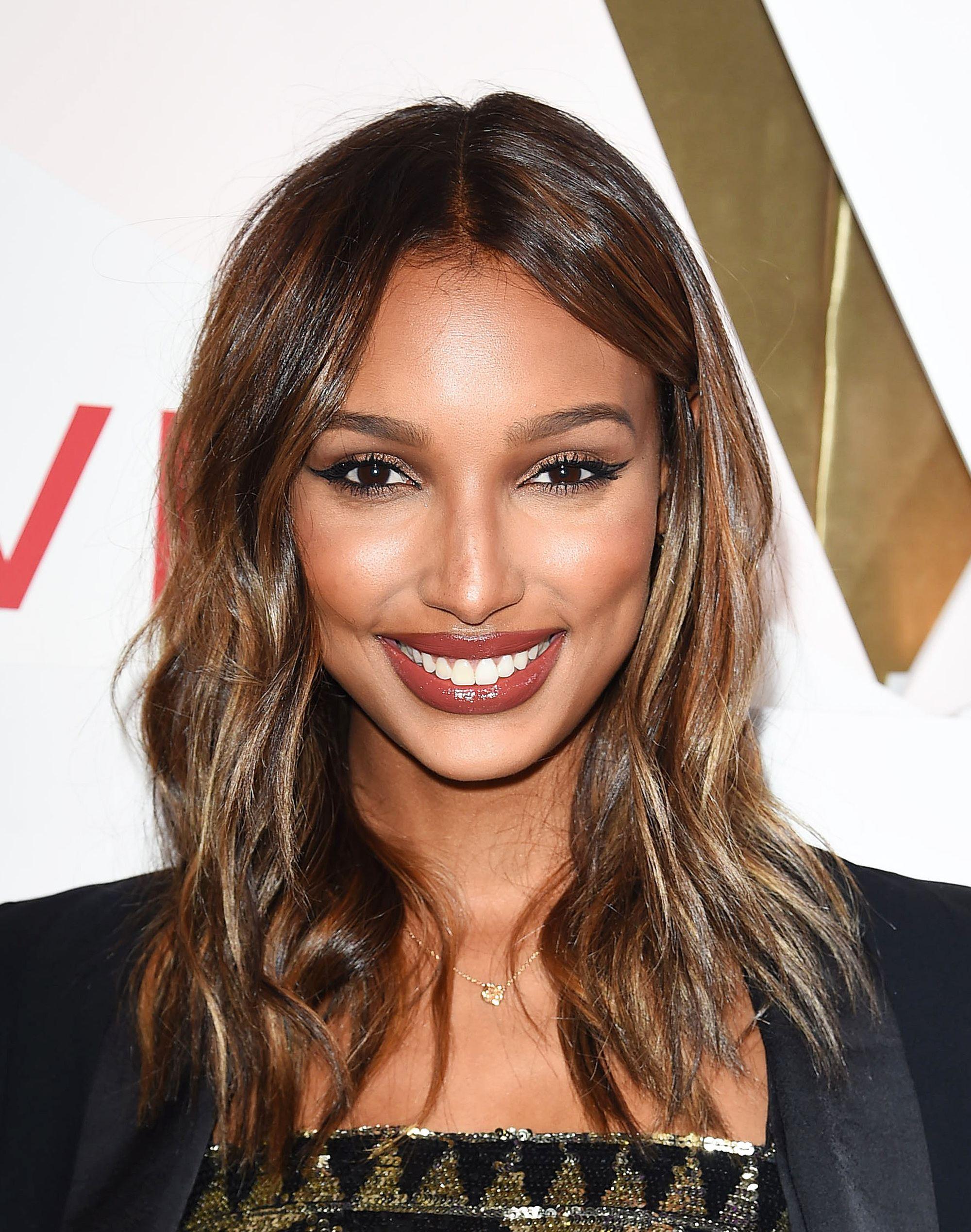 Jasmine Tookes avec des cheveux foncés aux épaules avec des reflets caramel sur le tapis rouge