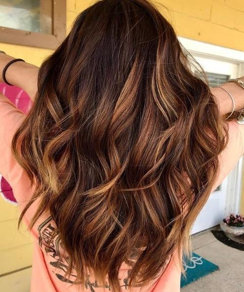 Les points forts du caramel : Vue de dos d'une femme aux cheveux caramélisés aux tons chauds, frisés en vagues