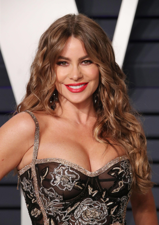 Sofia Vergara avec de longs cheveux caramel dulce de leche coiffés en boucles lâches sur le tapis rouge