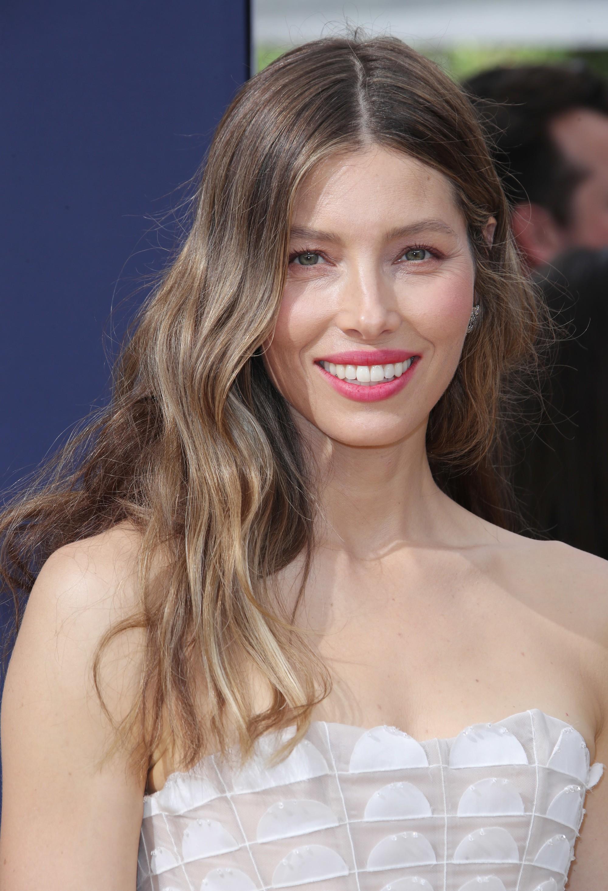 Jessica Biel, cheveux châtain cendré avec des cheveux caramel sable, portant un haut blanc sur le tapis rouge