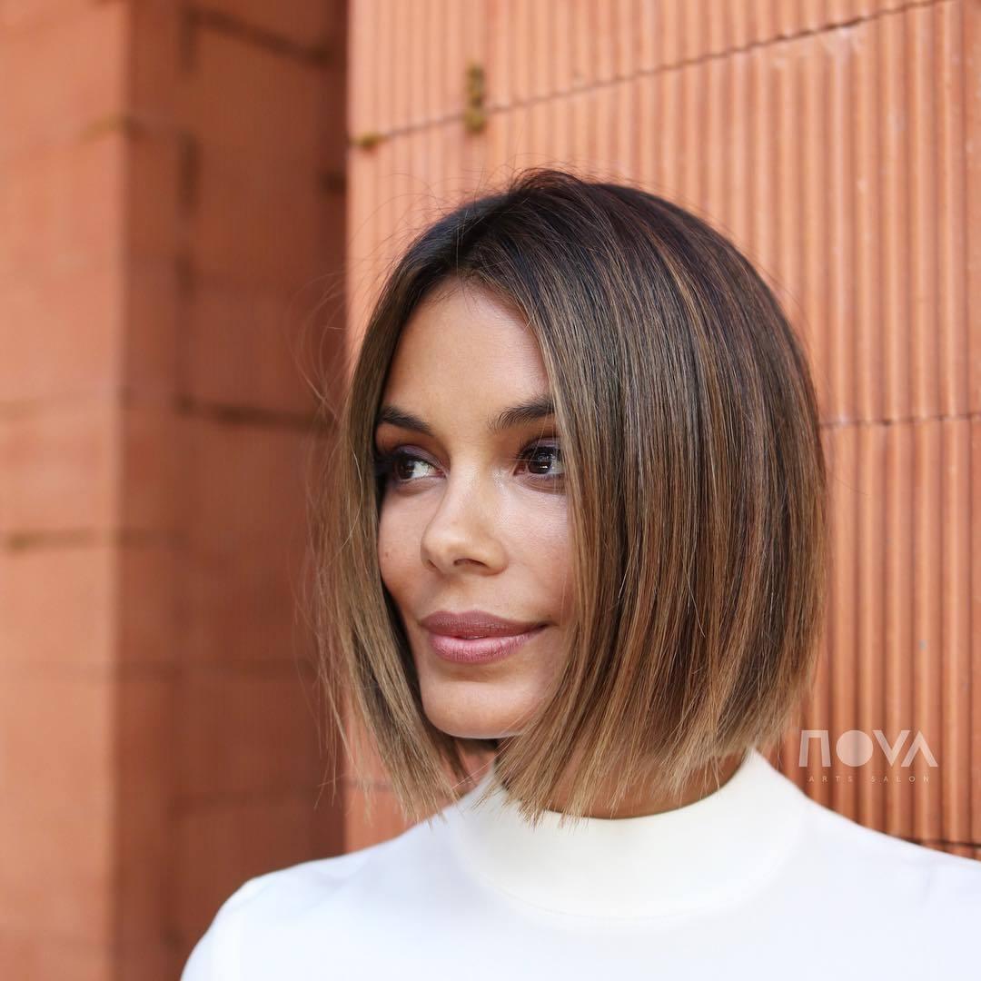 Les points forts du caramel : Femme aux cheveux bruns foncés à reflets caramel, portant du blanc et posant à l'extérieur