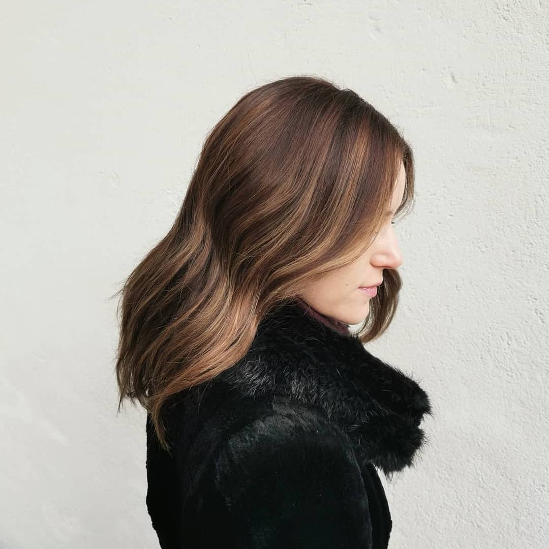 Femme aux cheveux brun foncé de longueur moyenne avec des lumières de brosse caramel