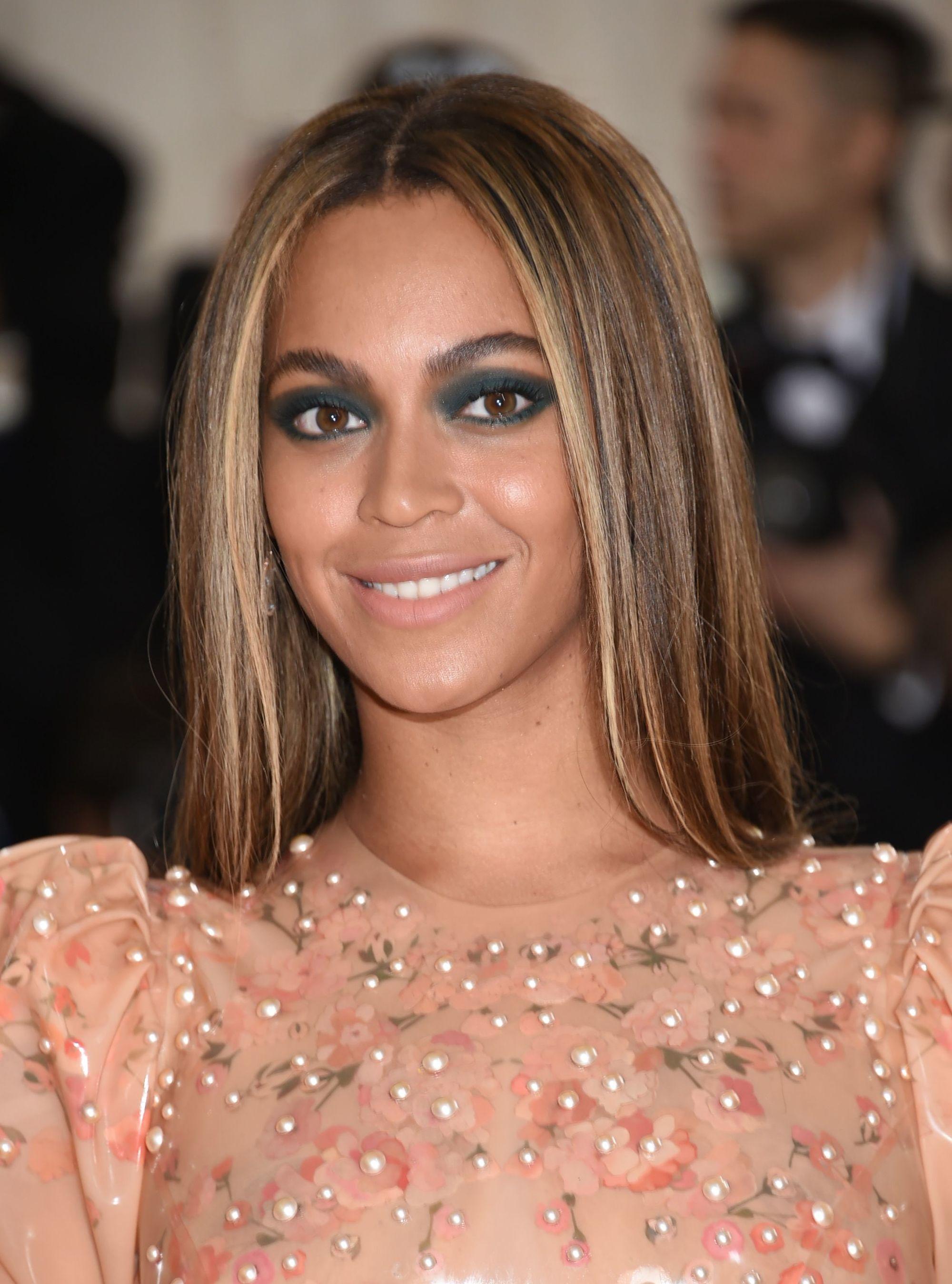 Beyonce aux longs cheveux raides de couleur brun caramel avec des reflets blonds, portant une robe en or rose sur le tapis rouge