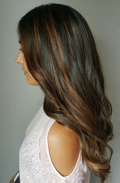 Les points forts du caramel : Vue de côté d'une femme aux longs cheveux foncés à reflets caramel, légèrement bouclés aux extrémités