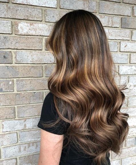 Les points forts du caramel : Longue chevelure brune ondulée avec balayage et reflets caramel