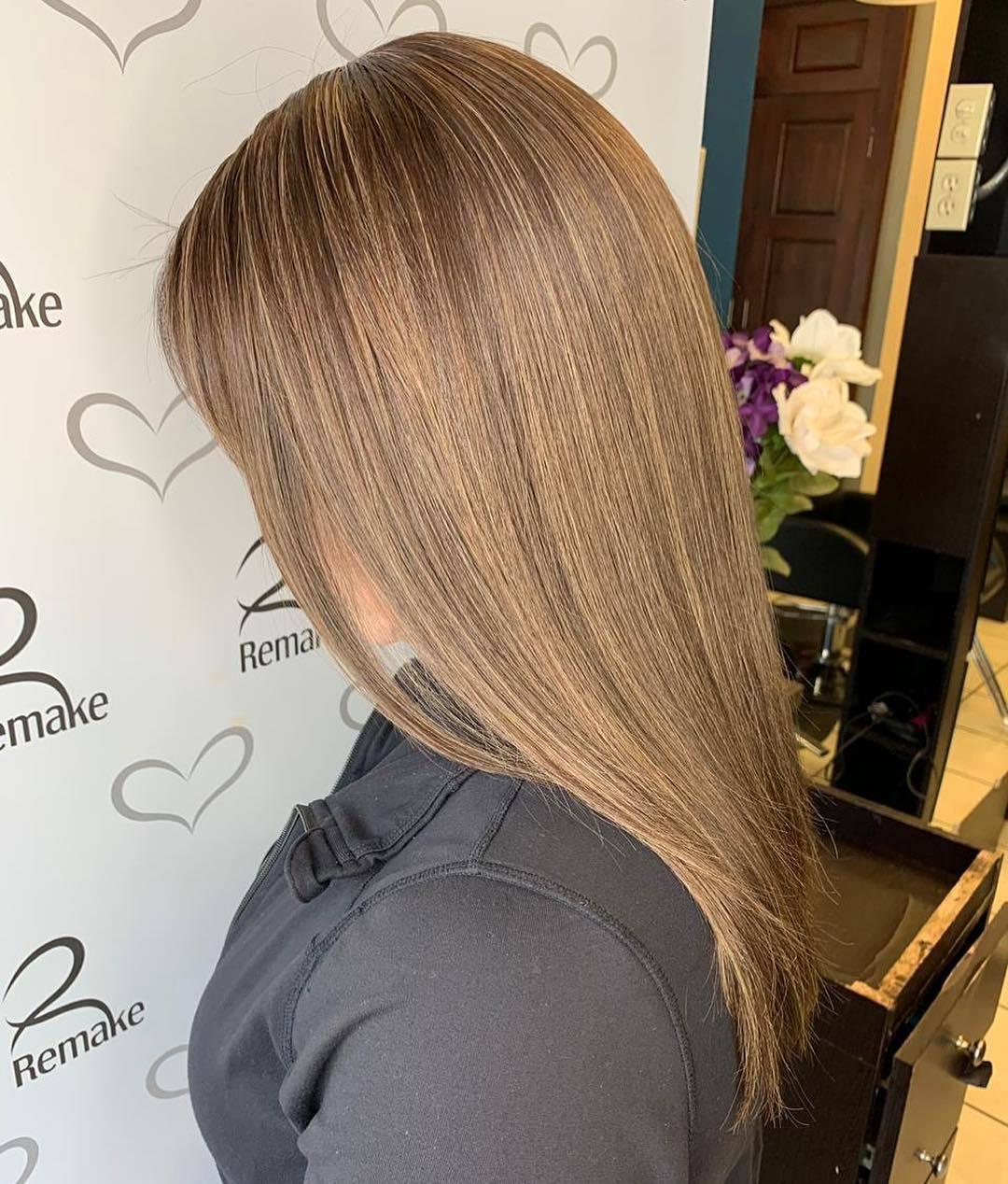 Photo d'une femme dans un salon avec des cheveux longs et raides au caramel