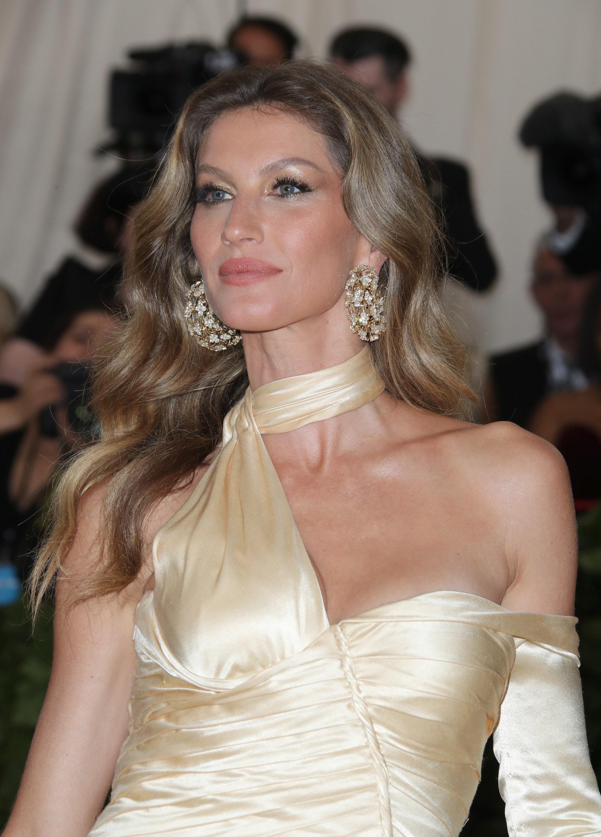 Gisele Bundchen aux longs cheveux châtains avec des reflets caramel, portant une robe de satin sur le tapis rouge