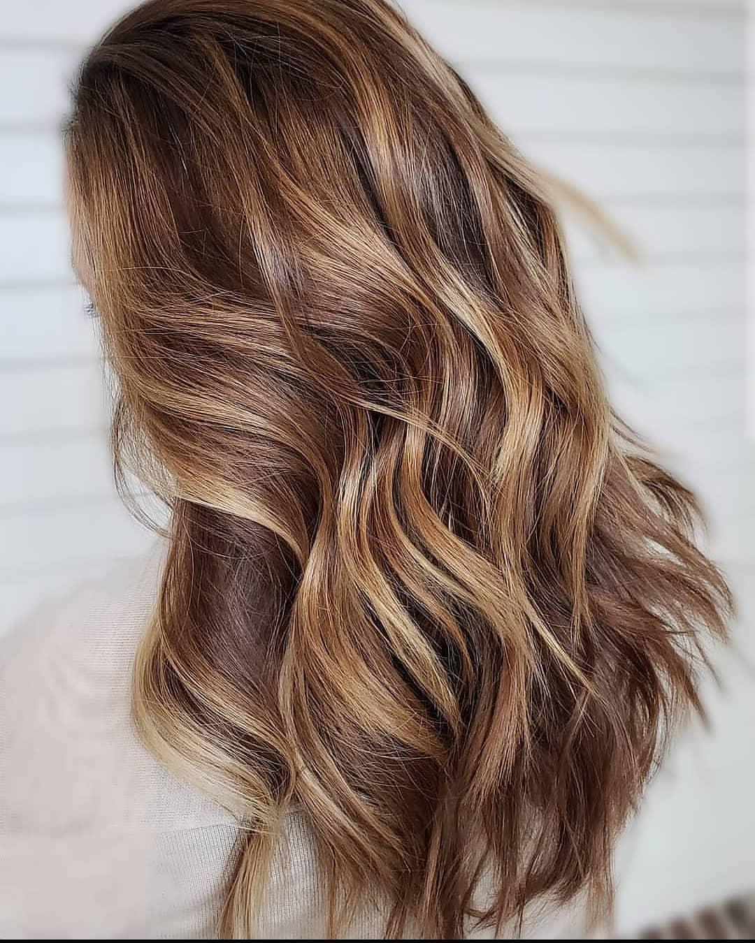 Femme aux cheveux châtain clair avec des reflets caramel et miel