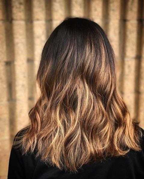 Les points forts du caramel : Gros plan sur des babylights brunes caramel sur des cheveux ondulés à la longueur des épaules