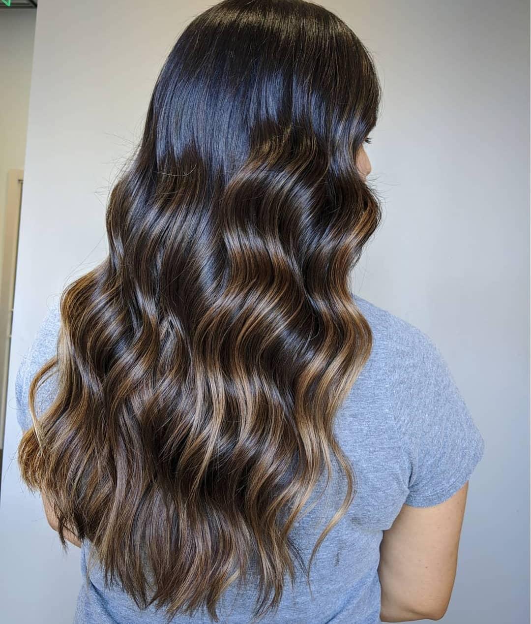 Femme aux cheveux brun foncé avec de subtils accents de caramel