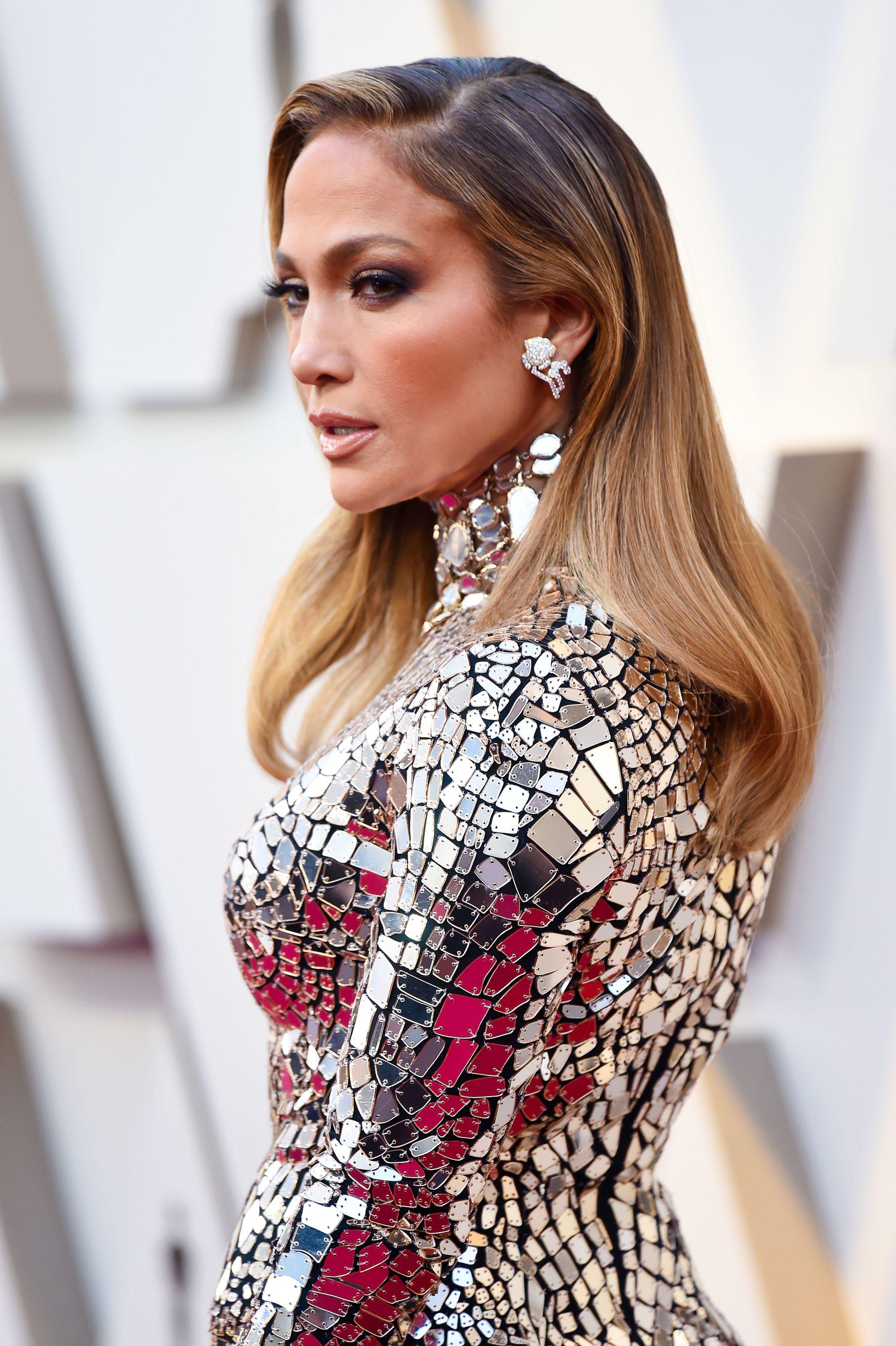 Jennifer Lopez sur le tapis rouge avec de longs cheveux lisses de couleur caramel foncé à clair, portant une tenue pailletée sur le tapis rouge