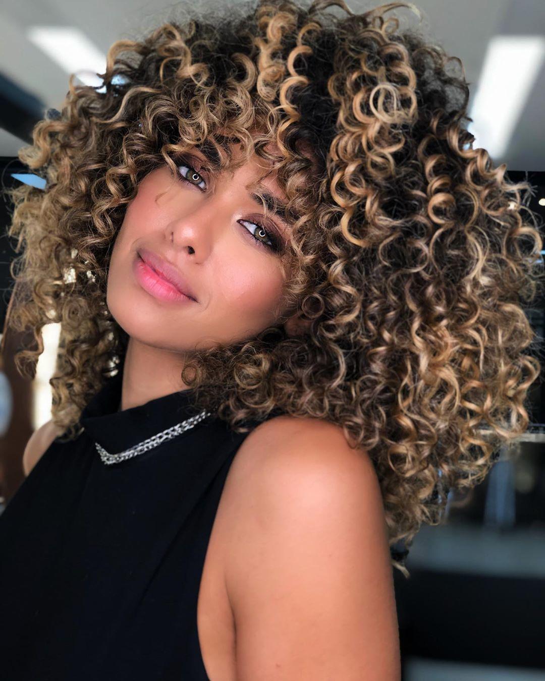 Femme aux cheveux bouclés naturels avec des reflets caramel