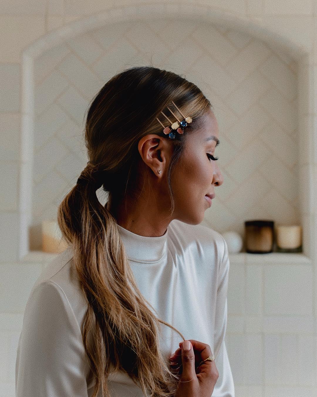 Femme aux longs cheveux brun foncé à reflets caramel, coiffée en queue de cheval basse, portant des barrettes et posant dans une chambre à coucher