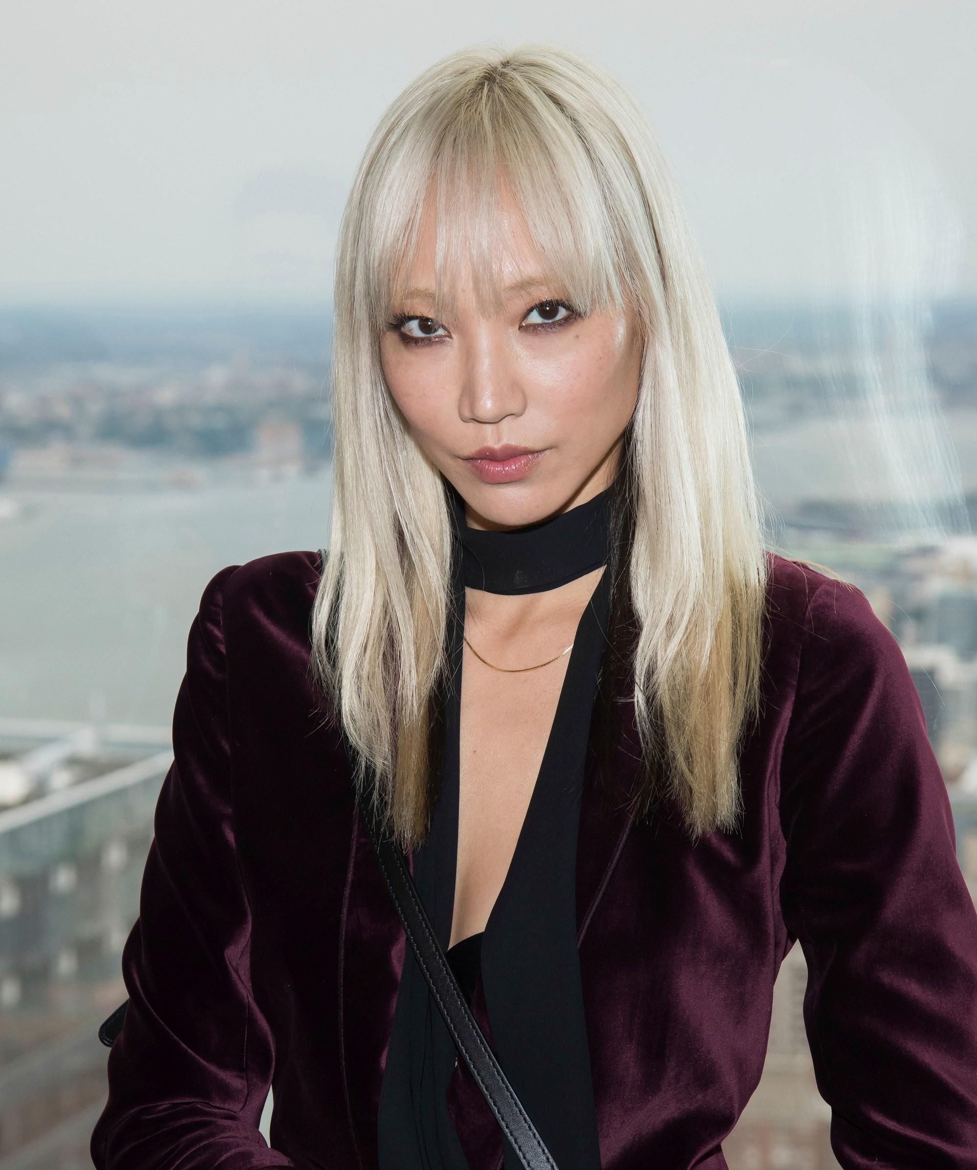Soo Joo Park avec des cheveux blonds décolorés et raides avec une frange