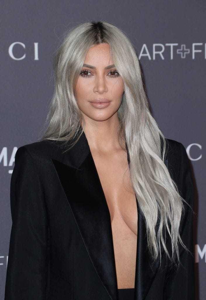 Nuances de cheveux blonds : Kim Kardashian West avec de très longs cheveux blonds argentés ondulés portant une robe blazer noire.