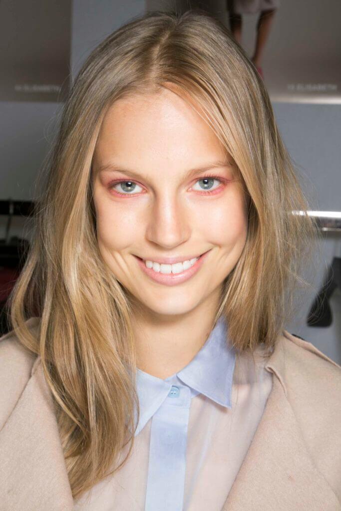 Nuances de cheveux blonds : Femme aux cheveux blonds raides et méchés, portant une chemise bleu clair avec une veste beige.