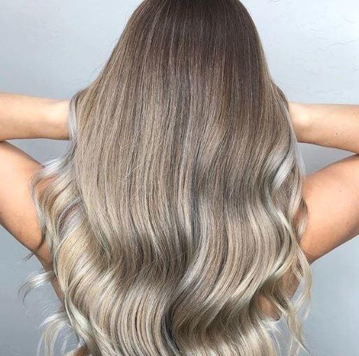 Nuances de cheveux blonds : Femme aux longs cheveux ondulés de blond cendré qui balaye ses cheveux en passant ses mains.