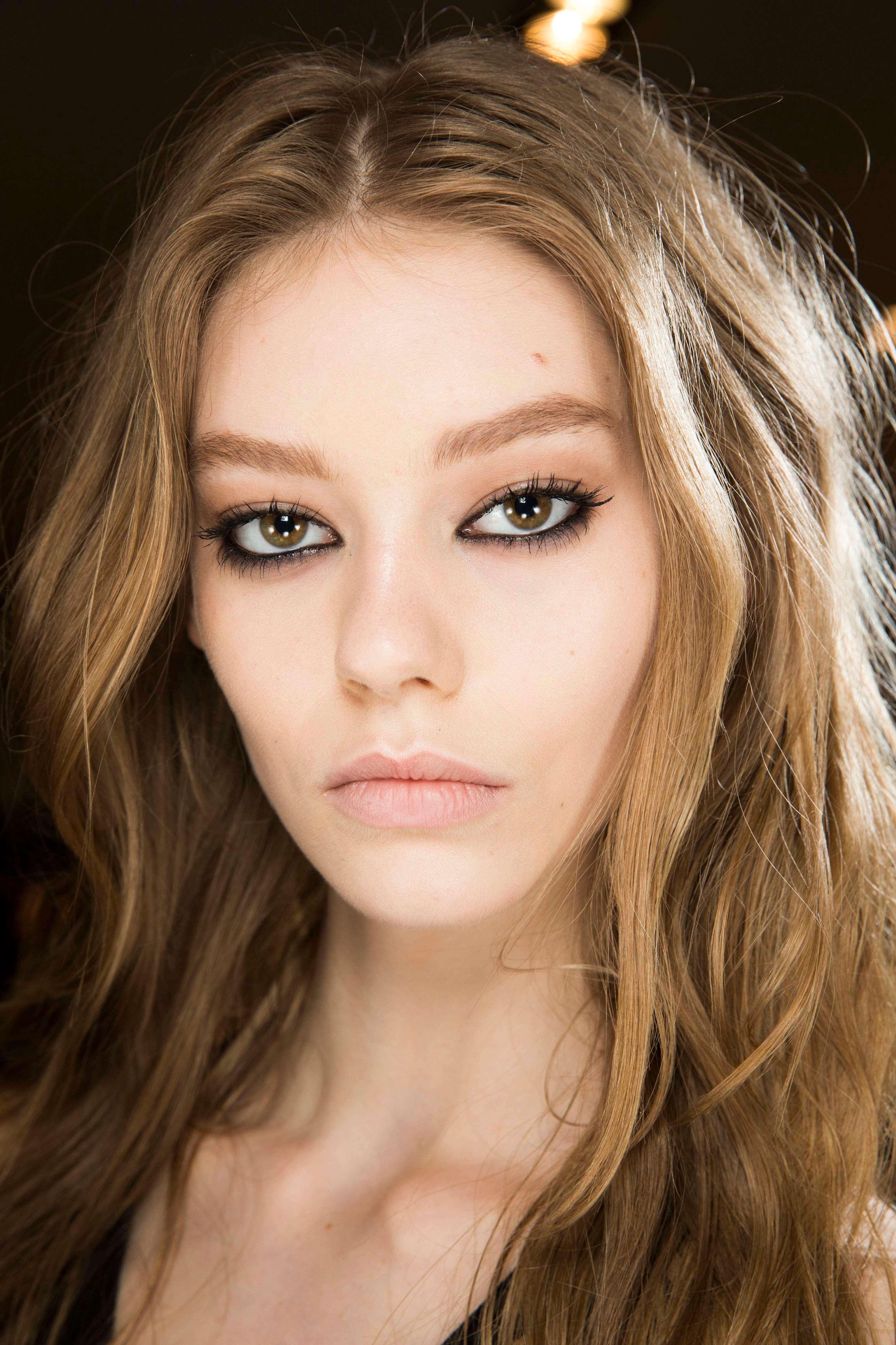 Nuances de cheveux blonds : Femme aux cheveux bruns ondulés d'un blond foncé et portant un maquillage épais pour les yeux.