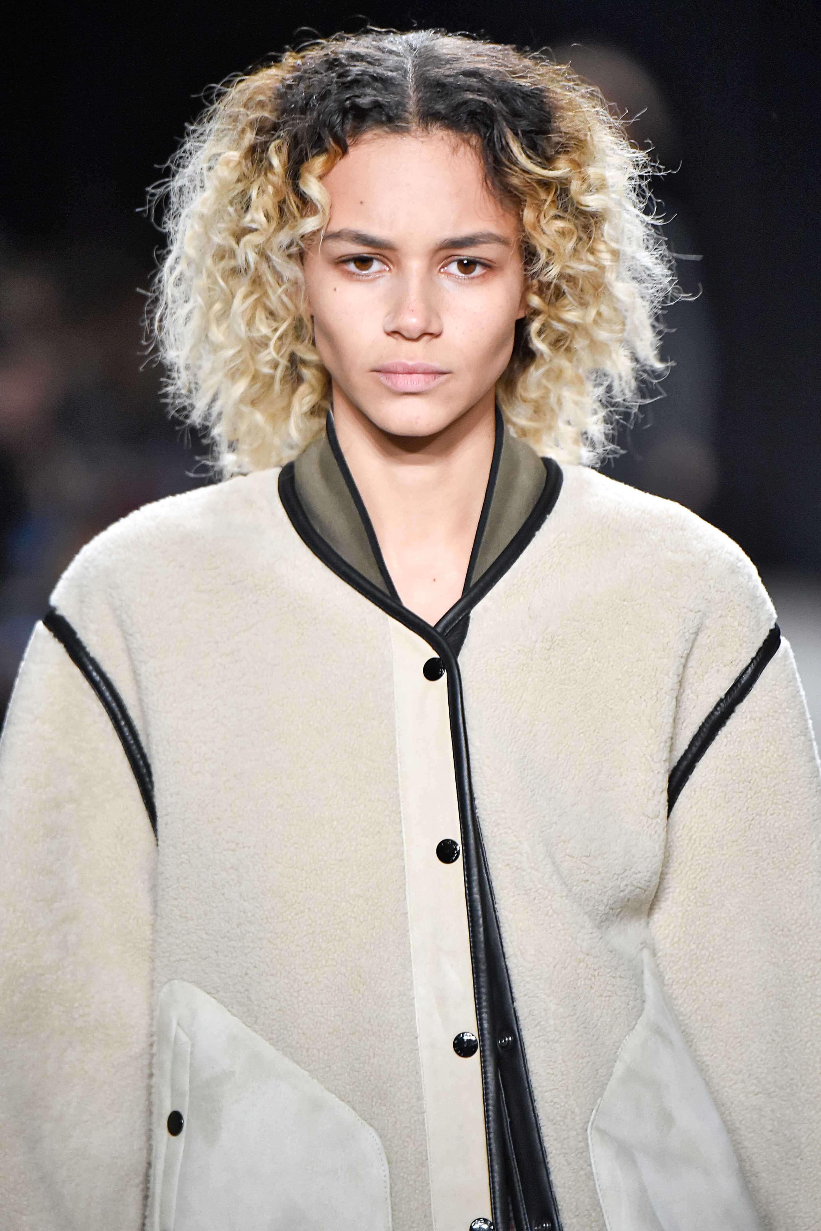 Nuances de cheveux blonds : Femme aux cheveux blond platine naturellement bouclés avec des racines brun foncé sur une piste de décollage, portant un blouson de bombardier.