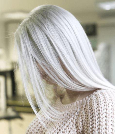 Nuances de cheveux blonds : Femme aux cheveux longs et raides d'un blond glacé, portant un pull en tricot beige.