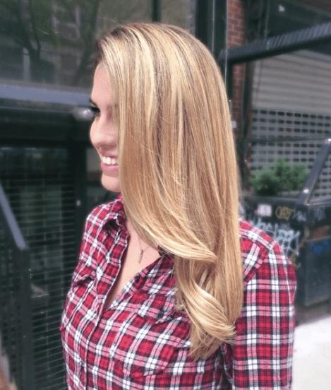vue de côté d'une femme aux cheveux longs et usés d'une couleur blonde naturelle