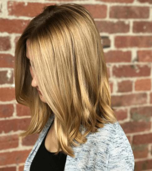 Nuances de cheveux blonds : Femme aux cheveux blonds caramélisés à longueur d'épaule avec une légère ondulation.