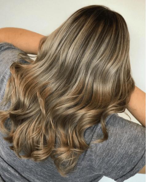 vue arrière d'une femme aux cheveux longs et aux différentes nuances de blond